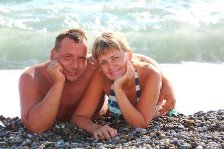 middleaged pair lie on pebble beach photo