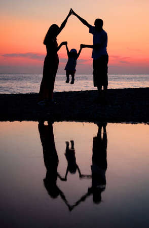 Silhouettes of parents with child against  sea decline photo
