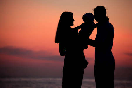 Silhouettes of parents with child on hands against  sea decline photo