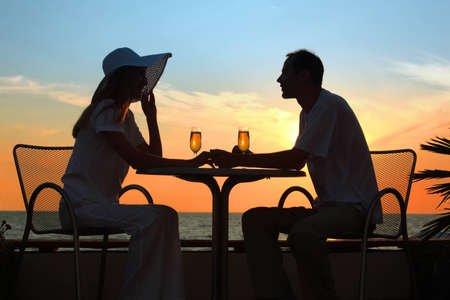 outdoor restaurant: Female and mans silhouettes on sunset sit at table with two glasses outdoor Stock Photo