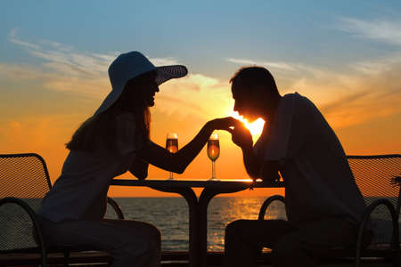 man kisses  hand to  woman on sunset behind  table outside photo