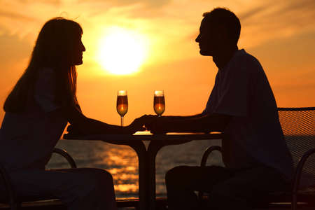 Female and mans silhouettes on sunset sit at table with two glasses outdoor, holding for hands photo