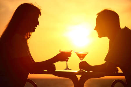man and woman clink glasses on sunset outside and talking photo