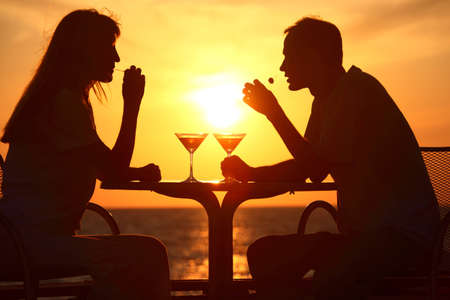 Female and mans silhouettes on sunset sit at table with two glasses and olives outdoor photo