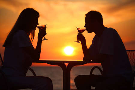 Female and mans silhouettes on sunset  drink from glasses photo