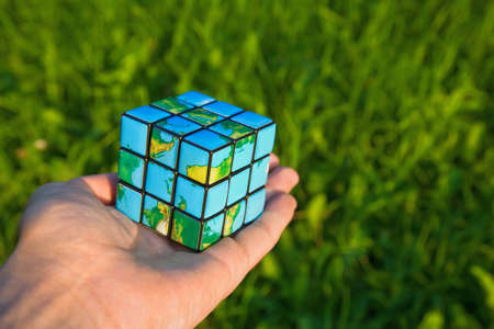 breakable: Cube in the manner of planets land on palm on background of the herb Stock Photo