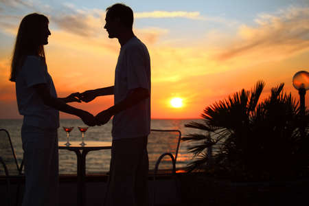 woman and man keep for hands against sunset on sea photo