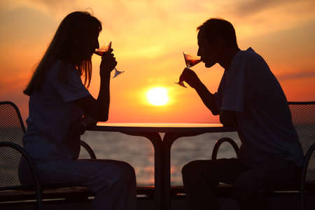 Female and mans silhouettes on sunset behind table drink from glasses photo