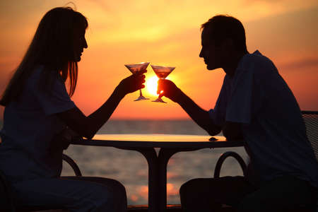 man and woman clink glasses on sunset outside photo