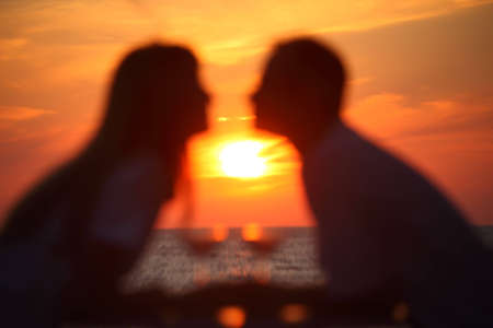 Blurred in boke female and mans silhouettes on sunset sit at table with two glasses outdoor photo