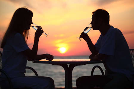 Female and mans silhouettes on sunset behind table drink from glasses, focus on man photo