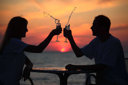 silhouettes of man and woman splash out drink from glass on sea sunset. focus on man photo