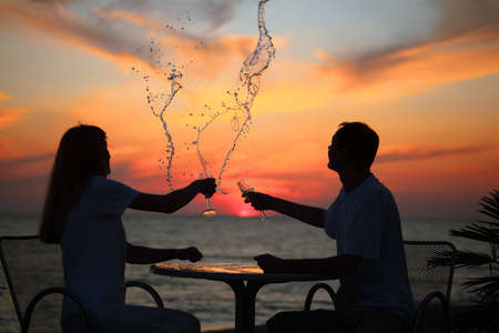 silhouettes of man and woman splash out drink from glass on sea sunset photo