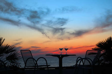 table with two glasses of wine on sunset on sea outdoor photo