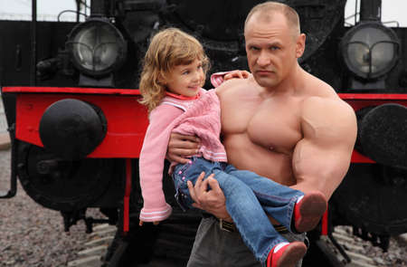 aegis: strong shirtless man  on railroad with little girl on hands Stock Photo