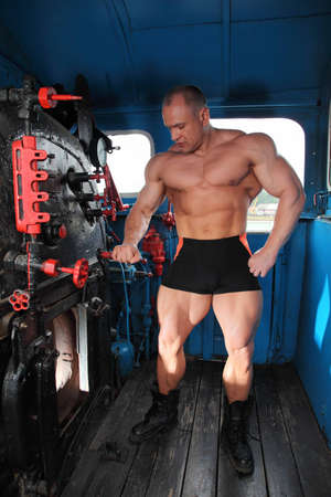 athlete in locomotive cabin full body with open furnace photo