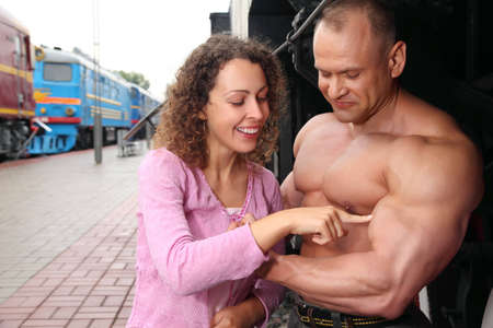 young woman  touches by finger  biceps of athlete photo