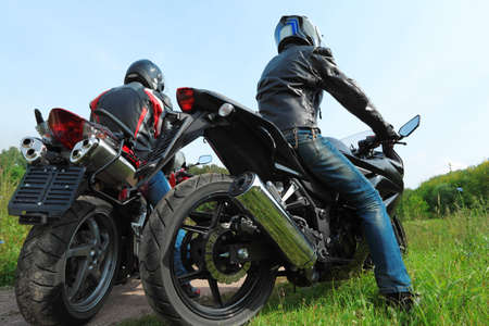 two wheel: two motorcyclists standing on country road, back view