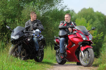 two motorcyclists standing on country road, without helmets photo