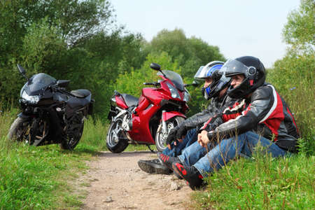 two motorcyclists sitting on country road near bikes photo