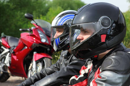 closeup of two motorcyclists sitting on country road near bikes photo
