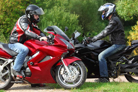 two motorcyclists standing on country road, side view, focus on right man photo