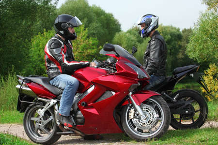 two motorcyclists standing on country road, side view photo
