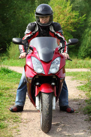 motorcyclist standing on country road photo
