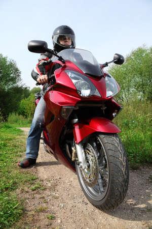 motorcyclist: motociclista de pie en la carretera del pa�s, portarretrato  Foto de archivo