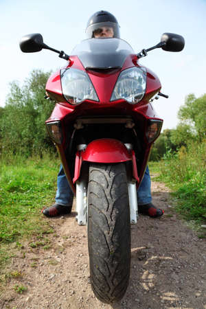 motorcyclist standing on country road, closeup, front view photo