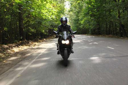 the rider: motociclista si va sulla strada, vista frontale Archivio Fotografico