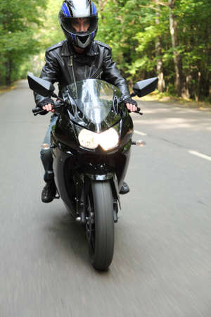 motorcyclist goes on road, front view photo