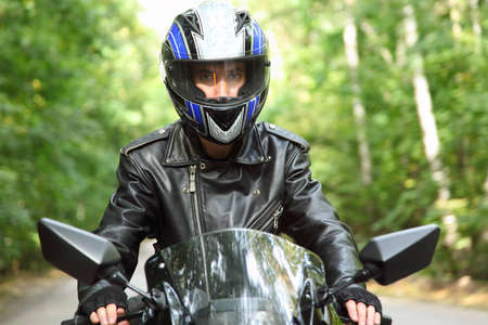 motorcyclist goes on road, front view, closeup photo