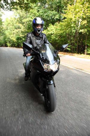 motociclista: motociclista si va sulla strada, vista frontale Archivio Fotografico