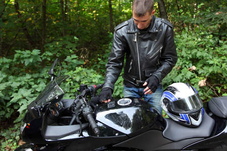motorcyclist and his bike in forest photo