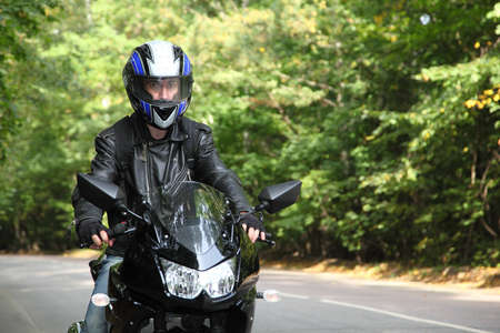 motorcyclist goes on road photo