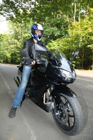 motorcyclist standing on road photo