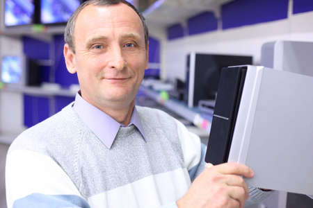elderly man in shop of radio engineering with loudspeaker in hands Stock Photo - 7831789