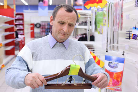 elderly man in shop with hanger for clothes in hands Stock Photo - 7831865