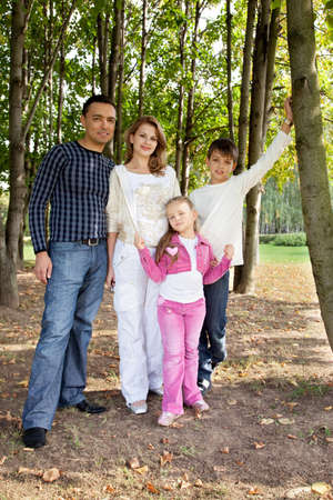 smiling happy family of four in park  photo
