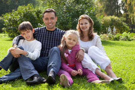 happy family of four persons outdoors photo