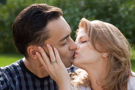 married couple kissing outdoors