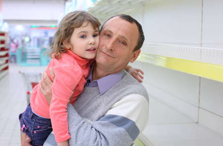 elderly man at empty shelves in  shop with child on hands Stock Photo - 7831824