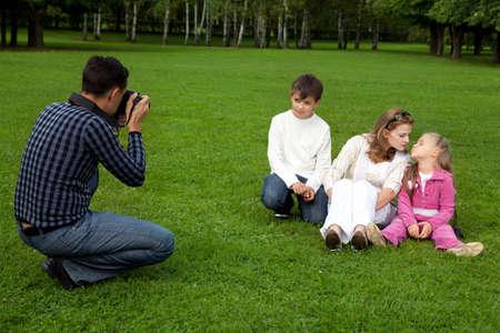 man photographes his family outdoors photo