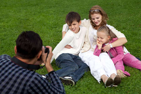 man photographes his family outdoors photo
