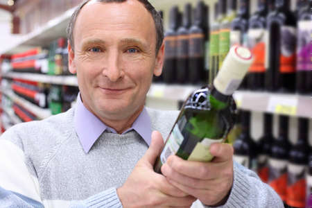 happy elderly man in shop with wine bottle in hands Stock Photo - 7831949