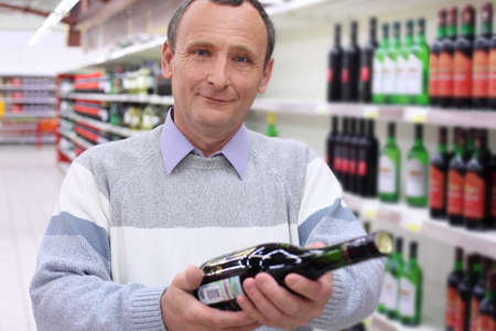 happy elderly man in shop with wine bottle in hands Stock Photo - 7831926