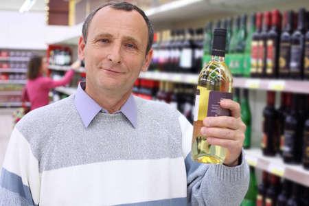 elderly man in shop holds wine bottle in hand Stock Photo - 7831928