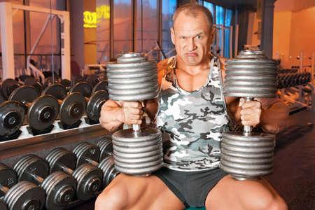 bodybuilder training: strong bodybuilder training muscles in gym
