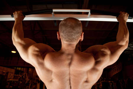 muscular body: bodybuilder back pull-up in training room